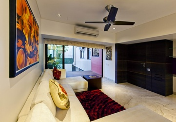 Son's suite with white pristine sofa - Photography by Esha Daftari