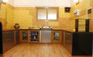 Kitchen With Wooden Flooring and Yellow Wall Tiles